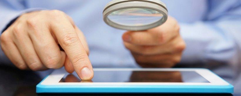 man using magnifying glass to look at ipad