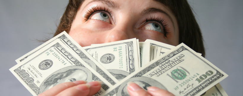 woman fanning out hundred dollar bills covering her face