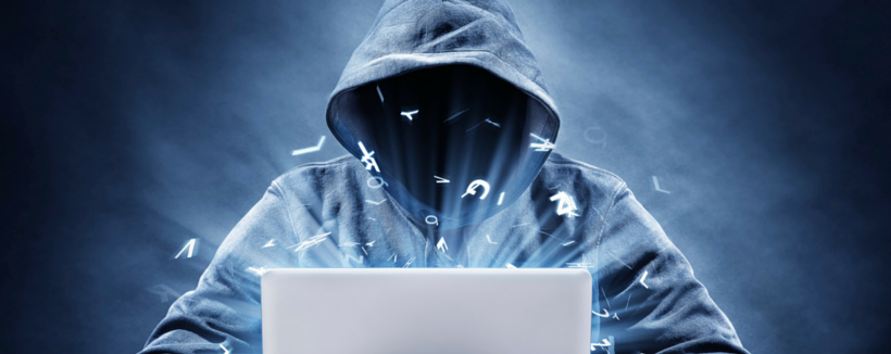person wearing hoodie and face is hidden programming on laptop
